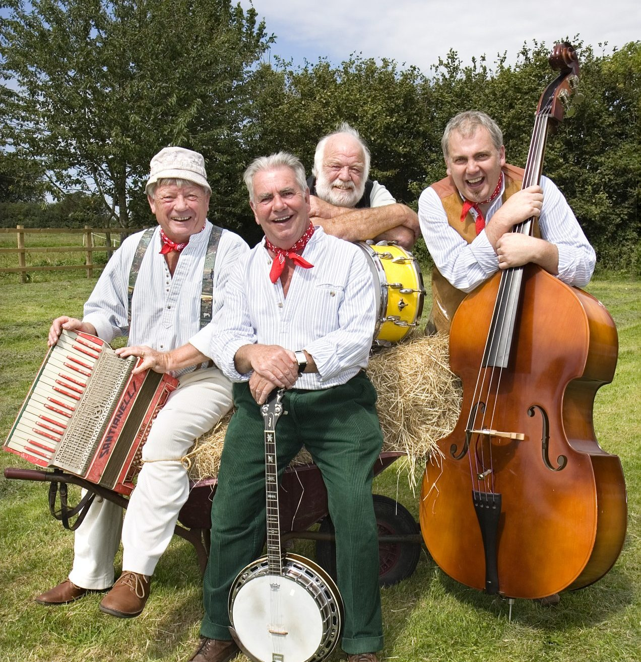 The Wurzels band sitting in a field with their instruments